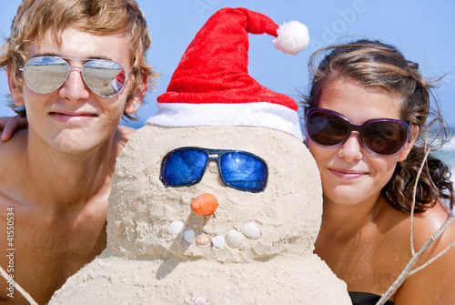 Portrait of couple having fun at beach with sandman