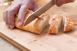 Male hands slicing rustic, home-baked peppercorn bread.