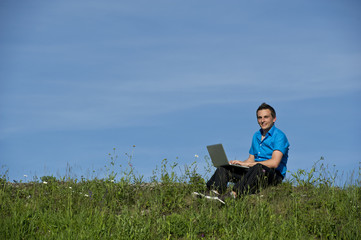 Business Mann sitzt in der Wiese mit Laptop