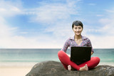 Beautiful woman with laptop at the beach