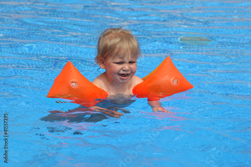 Toddler girl learning how to swim with swimmies