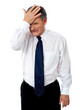 Sad old corporate man with hand on head