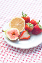lemon, fig and strawberries on a plate