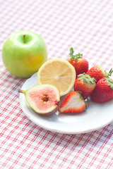 apple, lemon, fig and strawberries on a plate