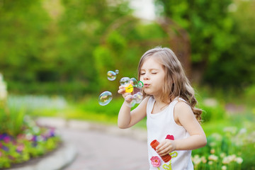 Cute curly girl  blowing  soap bubbles