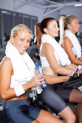 young woman drinking water while cycling in gym