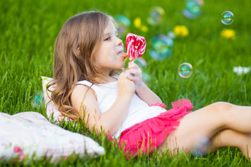 little girl with lollipop resting on the grass in summer day