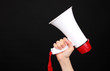 red and white megaphone in hand isolated on black