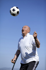 A retired player with walking stick to head a soccerball