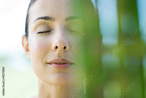 Woman closing eyes, smiling, bamboo in blurred foreground