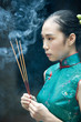Young woman wearing traditional Chinese clothing, holding up incense, side view