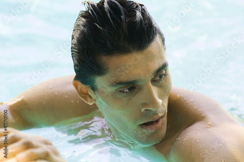 Man in swimming pool, looking over shoulder, close-up