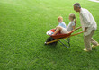 Man pushing two children in wheelbarrow