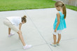 Girl drawing hopscotch game on driveway while second girl waits