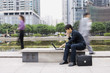 Businessman using laptop in office park, passers-by blurred in background