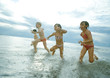 Four children racing in shallow water