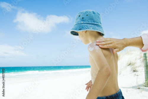 Mother putting sunscreen on child at beach