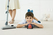 Little boy lying on the ground with toys, smiling at camera, mother vacuuming around him