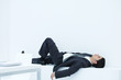 Businessman lying down on ledge in office