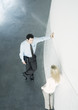 Businessman and businesswoman leaning against wall and talking, high angle view