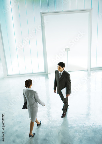 Woman walking to meet businessman in lobby