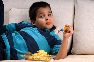 Little child eating while lying on sofa