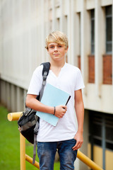 male teen high school student in front of school building