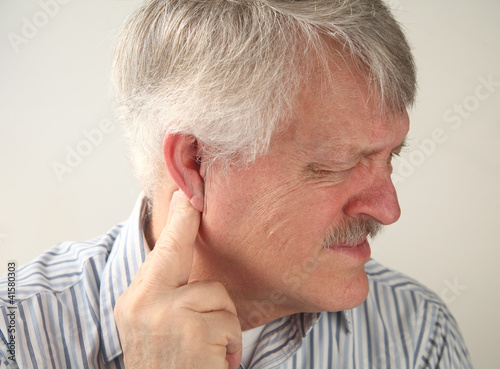 senior man suffers from pressure behind his ear