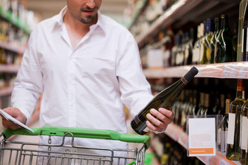 Male Shopper Looking at Liquor Bottle