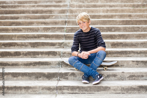 handsome teen boy sitting on skateboard