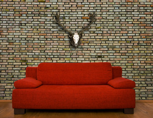 Rote Couch vor Backsteinwand