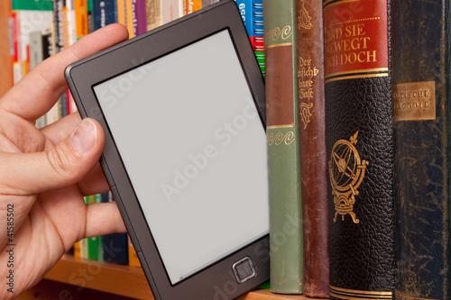 Leinwanddruck Bild eBook vs Buch, e-Reader aus einem Bücherregal ziehen