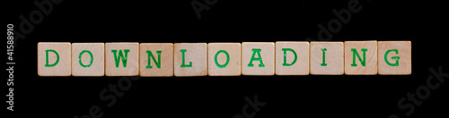 Green letters on old wooden blocks (downloading)