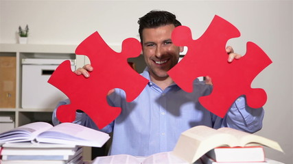 Student holding jigsaw puzzle pieces