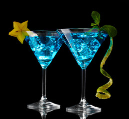 Blue cocktail in martini glasses on black background