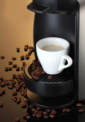 Espresso machine and cup of coffee on brown background