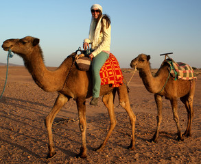 Young women ride on camel in desert
