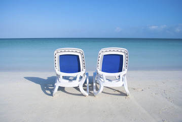 EMPTY BEACH CHAIRS IN FRONT OF OCEAN
