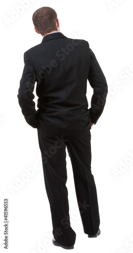 back view of Business man  looks ahead. Young guy in black suit