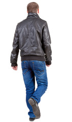 Back view of going  handsome man in jacket.  walking young guy i