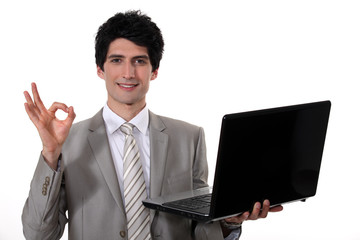 young handsome businessman with laptop making okay sign