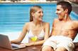 Paar mit Laptop am Pool
