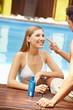 Paar im Urlaub trägt Sonnencreme auf