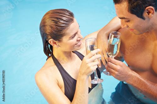 Mann und Frau trinken Sekt im Pool