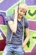 Style teen boy with headphones near graffiti background.
