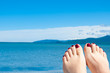 womans feet against sea and blue sky