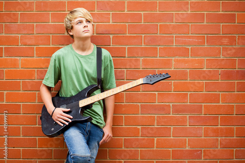 teen boy with guitar daydreaming