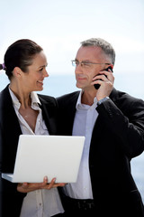 Business couple standing outdoors with a laptop and a phone