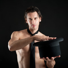 Young magician shirtless with cylinder against black background.
