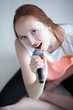 Red headed young woman holding with a microphone and sitting on